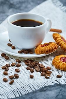 Uma xícara de café, biscoitos, grãos de café e canela.