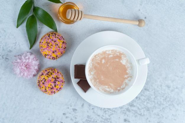 Uma xícara de café branco com mel e biscoitos pequenos com granulado.