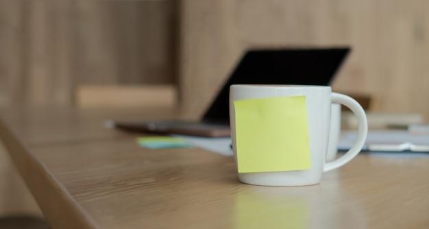 Uma xícara de café branco com uma nota pegajosa amarela em branco na xícara.