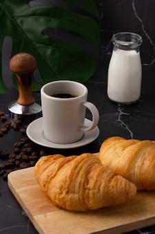 Uma xícara de café branco foi colocada ao lado de uma garrafa de leite e um croissant em uma tábua de cortar, grãos de café e moedores em um piso de mármore.