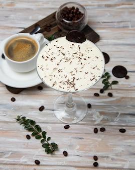 Uma xícara de café, café expresso com batido leitoso, creme de baunilha, decorado com gotas de chocolate.