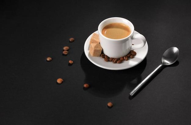 Uma xícara de café cappuccino em um fundo preto, grãos de café, pedaços de açúcar e uma colher de chá iluminada com luz brilhante.
