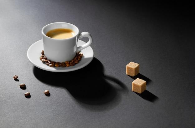 Uma xícara de café cappuccino em um fundo preto, grãos de café, pedaços de açúcar iluminado pela luz brilhante.