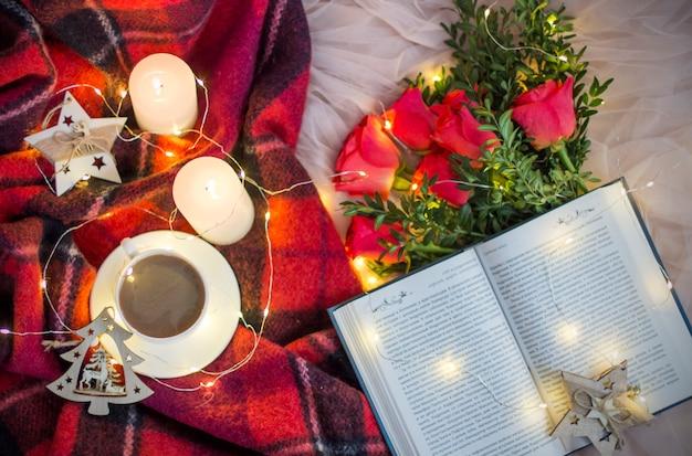 Uma xícara de café (chá), rosas vermelhas com buxo, um livro, velas, guirlandas