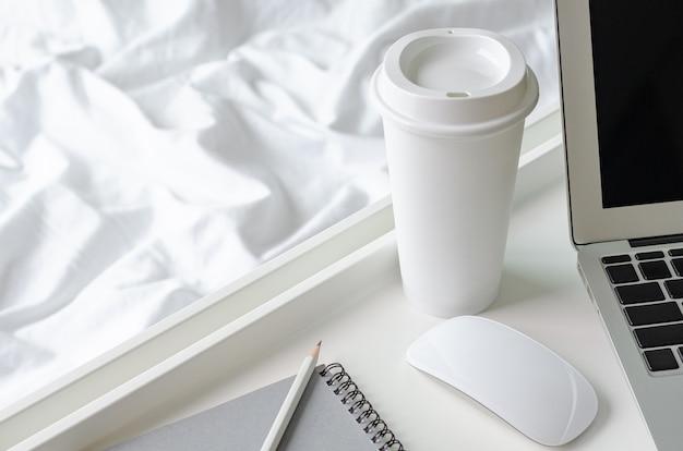 Uma xícara de café coloca ao lado do laptop e do mouse com a bandeja branca no cobertor bagunçado para trabalhar na cama.