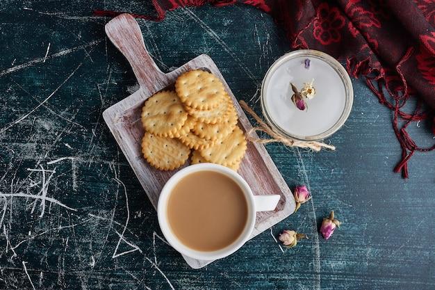Uma xícara de café com biscoitos em uma bandeja, vista superior.