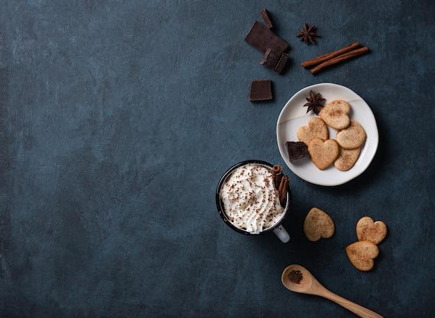 Uma xícara de café com creme e gotas de chocolate em uma mesa escura com biscoitos caseiros, chocolate e canela. vista superior, cópia espaço e plano