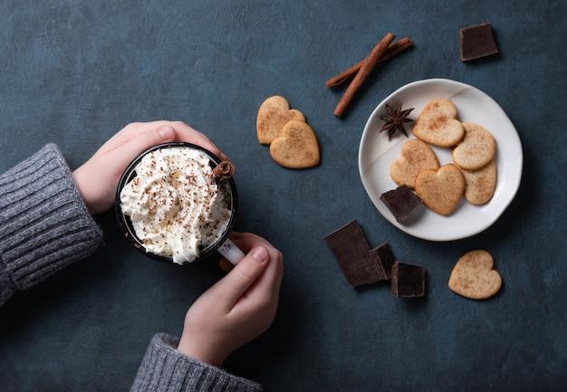 Uma xícara de café com creme e gotas de chocolate na mão da mulher sobre uma mesa escura com biscoitos caseiros, chocolate e canela. vista do topo