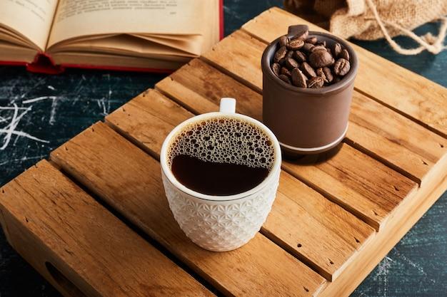 Uma xícara de café com espuma e grãos à parte.