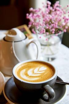 Uma xícara de café com espuma em um prato com talheres no contexto de um buquê de hiposphila