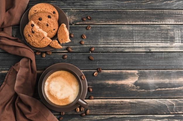 Uma xícara de café com espuma em uma madeira escura com biscoitos de aveia.