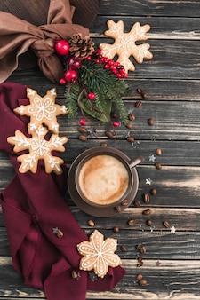 Uma xícara de café com espuma em uma madeira escura com pão de gengibre em forma de flocos de neve.
