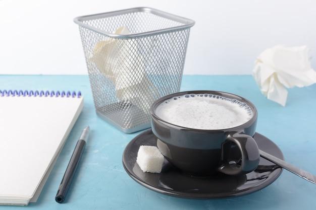 Uma xícara de café com espuma leitosa, um caderno aberto.