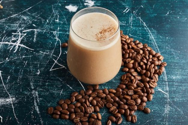 Uma xícara de café com feijão ao redor.