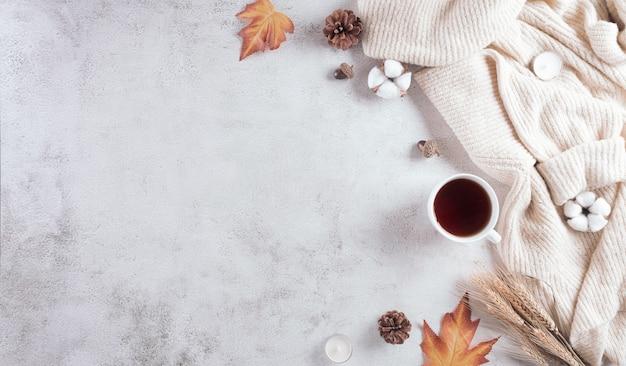Uma xícara de café com flores de algodão, folhas de outono e blusa com fundo de pedra