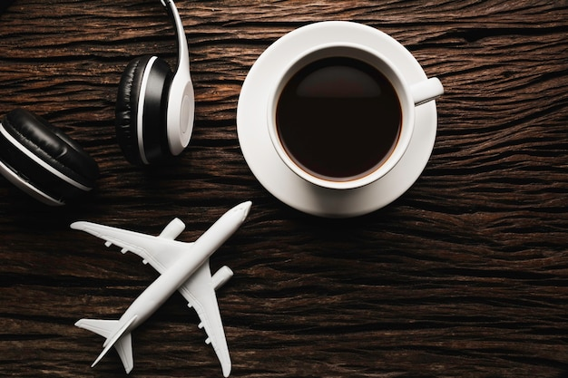 Uma xícara de café com fone de ouvido na mesa de madeira. vista superior do café com espaço de cópia. conceito de bebida.
