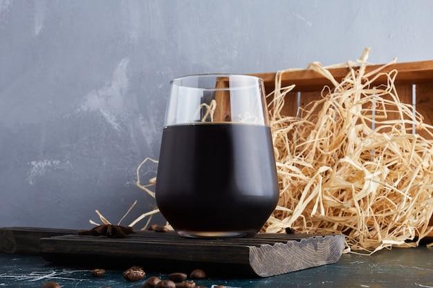 Uma xícara de café com grama seca ao redor.