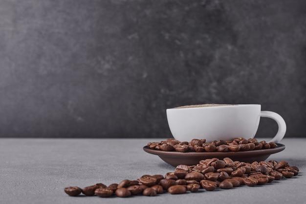 Uma xícara de café com grãos de arábica ao redor.