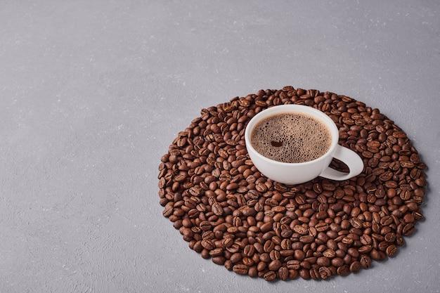 Uma xícara de café com grãos de arábica.