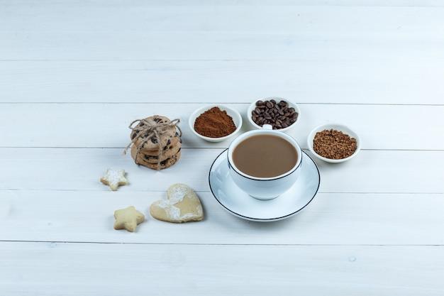 Uma xícara de café com grãos de café, café instantâneo, cacau, diferentes tipos de cookies no fundo da placa de madeira branca, vista de alto ângulo.