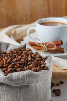 Uma xícara de café com grãos de café em um saco, canela seca vista lateral em uma plataforma e mesa branca
