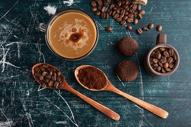 Uma xícara de café com grãos e biscoitos ao redor.