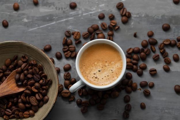 Uma xícara de café com grãos e uma colher de pau em fundo de cerâmica