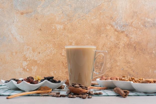 Uma xícara de café com laranjas secas e nozes em fundo de mármore. foto de alta qualidade