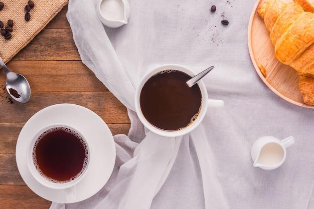 Uma xícara de café com leite, açúcar e pão croissant na mesa de madeira, vista superior