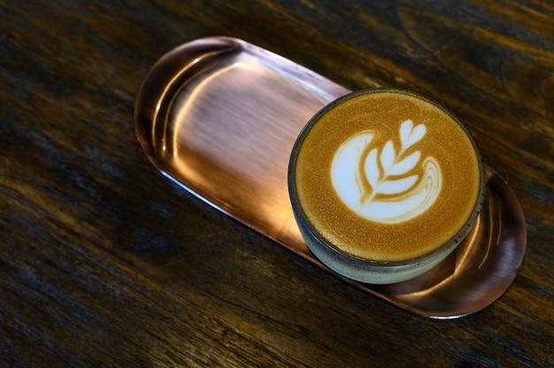 Uma xícara de café com leite arte em placa de latão na mesa de madeira