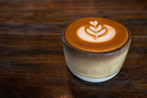 Uma xícara de café com leite arte na mesa de madeira