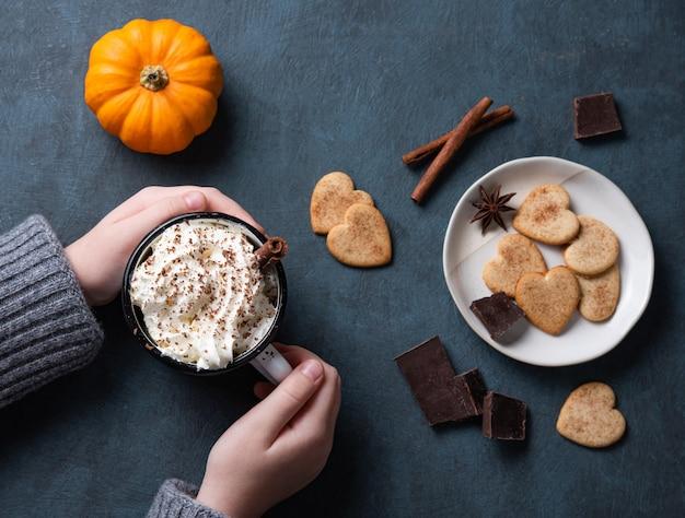 Uma xícara de café com leite de abóbora com creme na mão da mulher em uma mesa escura com biscoitos, chocolate e canela