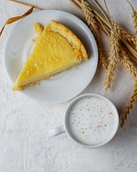 Uma xícara de café com leite e bolo caseiro com queijo cottage
