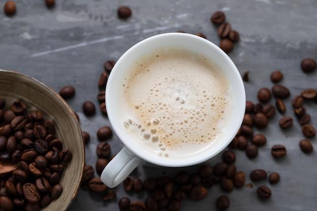 Uma xícara de café com leite e grãos com uma colher de pau em fundo de cerâmica
