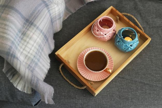Uma xícara de café com leite em uma bandeja de madeira com castiçais rosa e turquesa