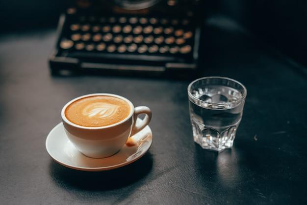 Uma xícara de café com leite em uma xícara de cerâmica e um copo de água