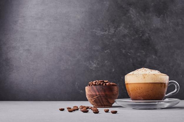 Uma xícara de café com leite isolada em fundo cinza.