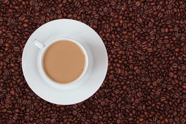 Uma xícara de café com leite no fundo de grãos de café