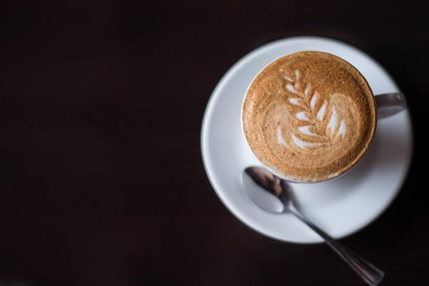 Uma xícara de café com leite quente art café na mesa de madeira