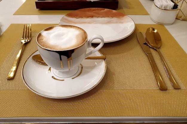 Uma xícara de café com leite quente com uma colher, garfo e faca na mesa do café