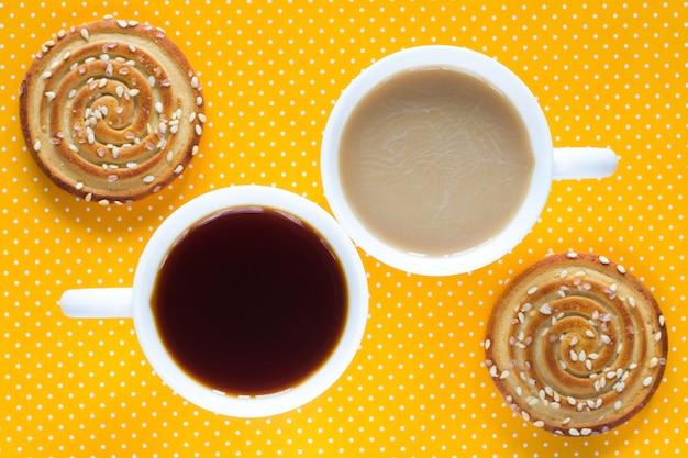 Uma xícara de café com leite. uma xícara de chá. dois biscoitos redondos com sementes de gergelim. vista do topo