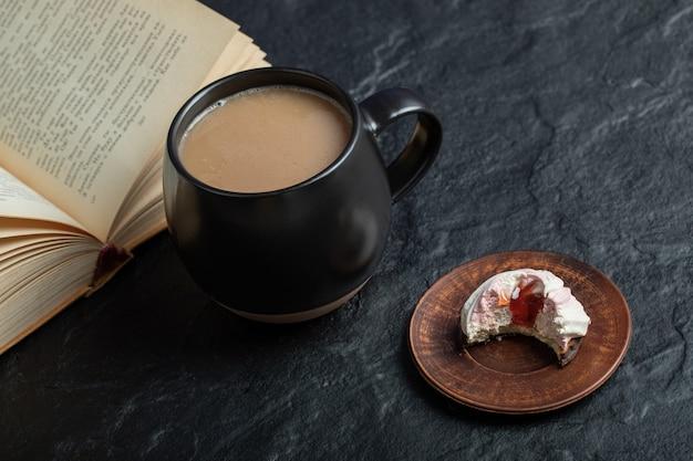 Uma xícara de café com livro e bolinho mordido.