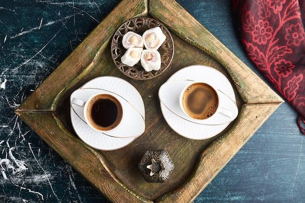 Uma xícara de café com lokum em uma bandeja de madeira.