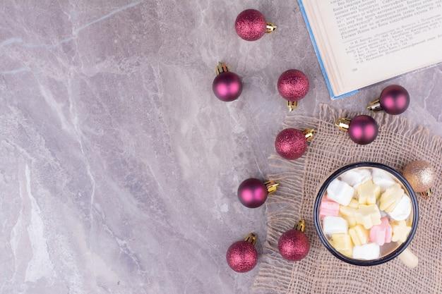 Uma xícara de café com marshmallows e bolas de natal ao redor.