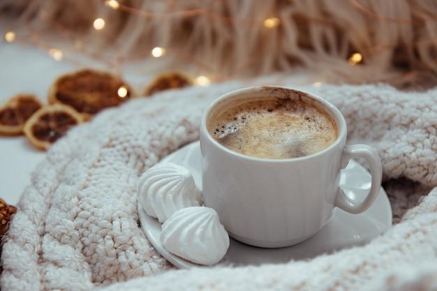 Uma xícara de café com merengues e um suéter de tricô - o conceito de conforto e aconchego.