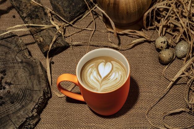 Uma xícara de café com padrão de coração em uma xícara branca com fundo de madeira.