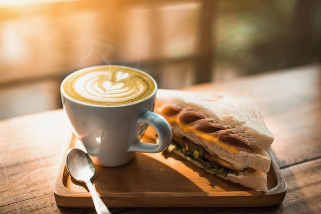 Uma xícara de café com padrão de coração em uma xícara branca e um sanduíche no fundo da mesa de madeira - imagem
