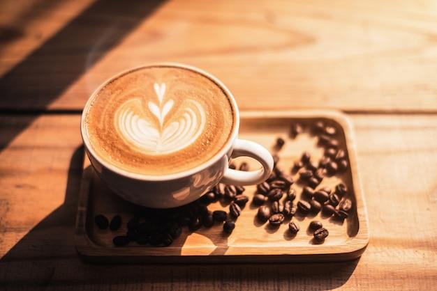 Uma xícara de café com padrão de coração em uma xícara branca no fundo da mesa de madeira