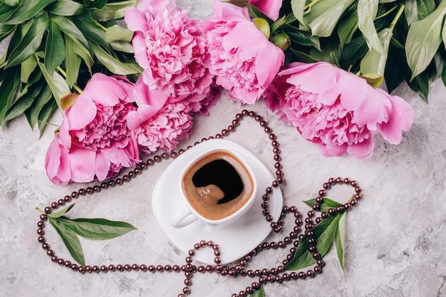 Uma xícara de café com pires e miçangas com flores de peônias rosa