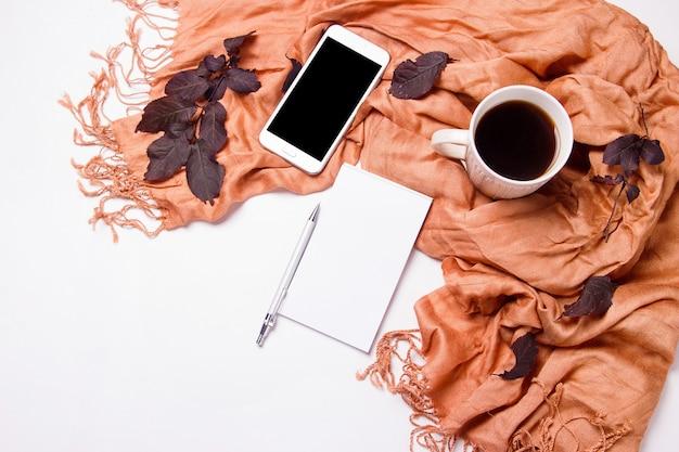 Uma xícara de café com um cachecol quente, bloco de notas, smartphone e folhas de outono